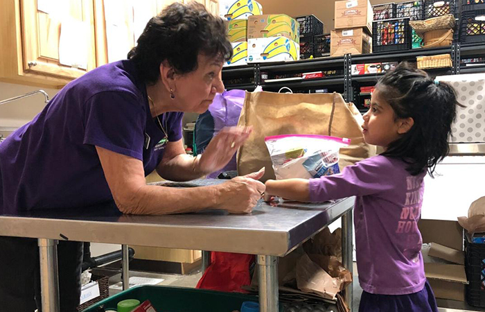 pam dipietro fro the foothills food bank with child